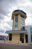 Cuenca, Ecuador - April 22, 2015: Yellow airport control tower standing next to terminal building Stock Images
