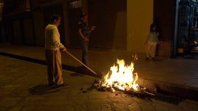 Cuenca, Ecuador - December 31, 2018 - Familie stookt straatvuur die bij middernacht op Nieuwjarenvooravond Oud Jaarbeeltenis bran stock video