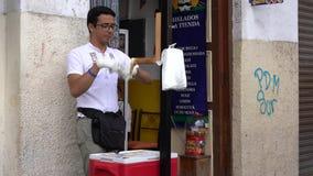 Cuenca, Ecuador - December 31, 2018 - Man maakt zout water taffy en verkoopt aan een vrouwenklant stock video