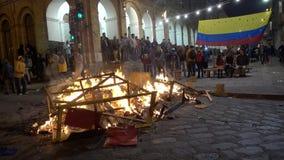 Cuenca, Ecuador - December 31, 2018 - Mensen let straat op vuur bij middernacht op Nieuwjarenvooravond met Ecuatoriaanse Vlag op  stock footage