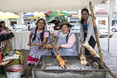 Cuenca, Ecuador / March 13, 2016 - Three women BBQ cuy for lunch. At an outdoor festival royalty free stock photos