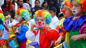 Group of little Children dressed in colorful costumes as clowns at the parade royalty free stock photography