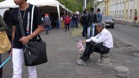Cuenca Ecuador - 20181003 - Cuenca självständighetsdagenfestival - brett skott av lottsedelförsäljaren som ropar hans krig arkivfilmer