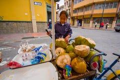 Cuenca Ekwador, Kwiecień, - 22, 2015: Młoda nastoletnia dziewczyna pracuje przy kokosowym bicyklu sklepem w centrum miasta, trzym Zdjęcia Royalty Free