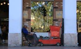 Cuenca, Ekwador -, 2-5-2019: Stary człowiek czyta gazetę podczas gdy czekać na klienta czyścić buty fotografia royalty free