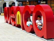 """Cuenca, Equateur, signe """"Cuenca """"de nom de ville Les enfants jouent autour du signe image libre de droits"""