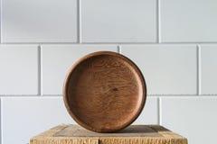 Cuenco abstracto de madera redonda en pilar de madera contra el fondo blanco Fotografía de archivo libre de regalías