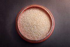 Cuenco anaranjado de semillas sanas en un fondo de Brown - top de la quinoa Imágenes de archivo libres de regalías