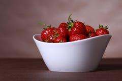Cuenco blanco de fresas en la tabla Imagen de archivo