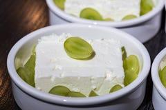 Cuenco blanco del desierto con queso del ` s del pío y uvas verdes como postre antes de asar a la parrilla en el horno Foto de archivo libre de regalías