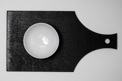 Cuenco blanco en tablero negro imagen de archivo libre de regalías
