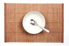 Cuenco blanco en una estera de bambú Fotografía de archivo libre de regalías