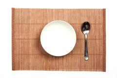 Cuenco blanco en una estera de bambú Fotos de archivo libres de regalías
