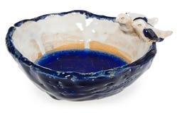 Cuenco blanco y azul de cerámica hecho a mano con dos pájaros que se sientan en su borde fotos de archivo