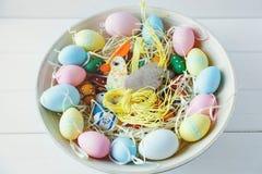 Cuenco con la naranja, amarillo de madera, el rosa y los huevos verdes en el fondo de madera blanco ¡Pascua feliz! Decoración fotos de archivo