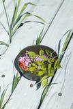 Cuenco con las flores en un patio de madera imagen de archivo