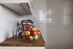Cuenco con las manzanas en la tabla de cocina Fotos de archivo libres de regalías