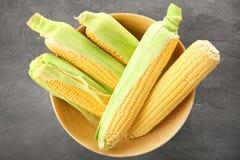 Cuenco con las mazorcas de maíz frescas Foto de archivo libre de regalías