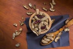 Cuenco con los cacahuetes con la c?scara y pelados con una cuchara en una superficie de madera fotos de archivo