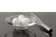 Cuenco con los huevos al lado de un batir Fotografía de archivo libre de regalías