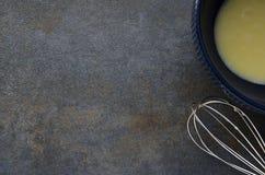 Cuenco con los huevos revueltos y el batidor en la tabla gris Preparación de la tortilla fresca fotografía de archivo libre de regalías