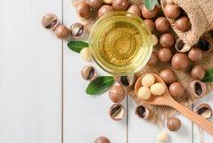 Cuenco de aceite de nuez de macadamia y de nueces de macadamia fotografía de archivo libre de regalías