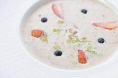 Cuenco de avena deliciosa del desayuno y mezclado con la fruta foto de archivo libre de regalías