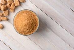 Cuenco de azúcar y de pedazos en la tabla de madera Imagen de archivo