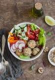 Cuenco de Buda del vegetariano - albóndigas de la quinoa y ensalada vegetal en el fondo de madera, visión superior Comida sana, v Imagen de archivo libre de regalías