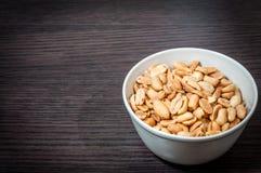 Cuenco de cacahuetes salados en la tabla de madera imagen de archivo libre de regalías