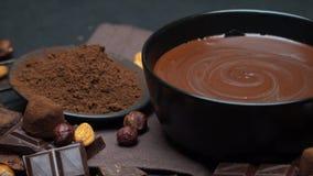 Cuenco de cerámica de crema del chocolate o chocolate, nueces y pedazos derretidos de chocolate metrajes