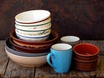 Cuenco de cerámica, de la arcilla, platos y taza hechos a mano vacíos en fondo de madera Diverso utensilio de la loza de barro de imagen de archivo libre de regalías