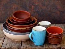 Cuenco de cerámica, de la arcilla, platos y taza hechos a mano vacíos en fondo de madera Diverso utensilio de la loza de barro de imagen de archivo