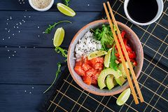 Cuenco de color salmón hawaiano del empuje de los pescados con arroz, el pepino, el rábano, las semillas de sésamo y la cal fotografía de archivo libre de regalías