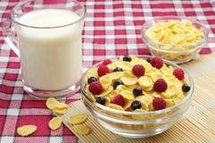 Cuenco de copos de maíz con las bayas y la taza de leche Fotografía de archivo