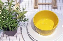 Cuenco de ensalada amarillo en las placas blancas dentro de una cocina moderna imágenes de archivo libres de regalías