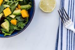 Cuenco de ensalada del aguacate del mango con la cal y la bifurcación Imagen de archivo