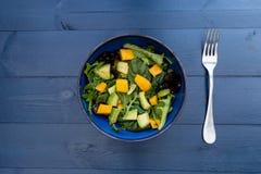Cuenco de ensalada del aguacate del mango en la tabla de madera azul Imagenes de archivo
