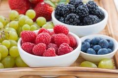 cuenco de frambuesas, de bayas frescas y de uvas verdes Foto de archivo