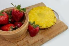 Cuenco de fresas con la rebanada de la pi?a en una tajadera imagen de archivo libre de regalías
