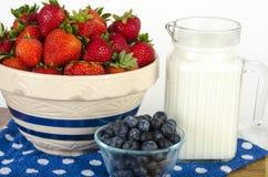Cuenco de fresas, de arándanos y de leche Fotos de archivo