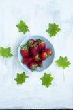 Cuenco de fresas frescas en la tabla blanca con las hojas verdes Fotografía de archivo