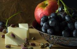 Cuenco de fruta antiguo con el racimo de uvas Fotos de archivo libres de regalías