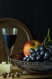 Cuenco de fruta antiguo con el racimo de uvas Imagen de archivo