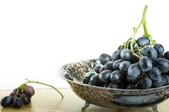 Cuenco de fruta antiguo con el racimo de uvas, en el fondo blanco Imagenes de archivo