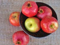 Cuenco de fruta de la caída con las manzanas y las granadas en el tablero de la mesa de la rota Imágenes de archivo libres de regalías