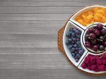 Cuenco de fruta en fondo de madera Fotos de archivo