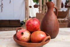 Cuenco de frutas de la granada y de jarra de la loza de barro Foto de archivo