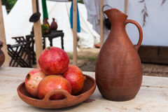 Cuenco de frutas de la granada y de jarra de la loza de barro Fotos de archivo