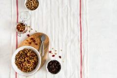 Cuenco de granola hecho en casa con las nueces y las frutas en el fondo de lino blanco Visión superior, espacio de la copia imagen de archivo